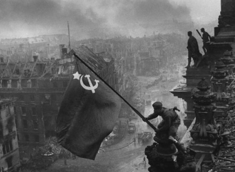 1945: Η Σοβιετική Ένωση ανακοινώνει την πτώση του Βερολίνου. Η κόκκινη σημαία με το σφυροδρέπανο κυματίζει στον ιστό του Ράιχσταγκ.